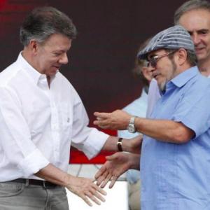 O presidente da Colômbia, Juan Manuel Santos, e o líder das Farc, Rodrigo Londoño, se cumprimentam na cerimônia que marca a conclusão da entrega das armas da guerrilha